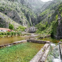 26509243_Canal_beneath_mountains_outside_walled_city_of_Kotor_in_Montenegro_Stock_Photo.jpg